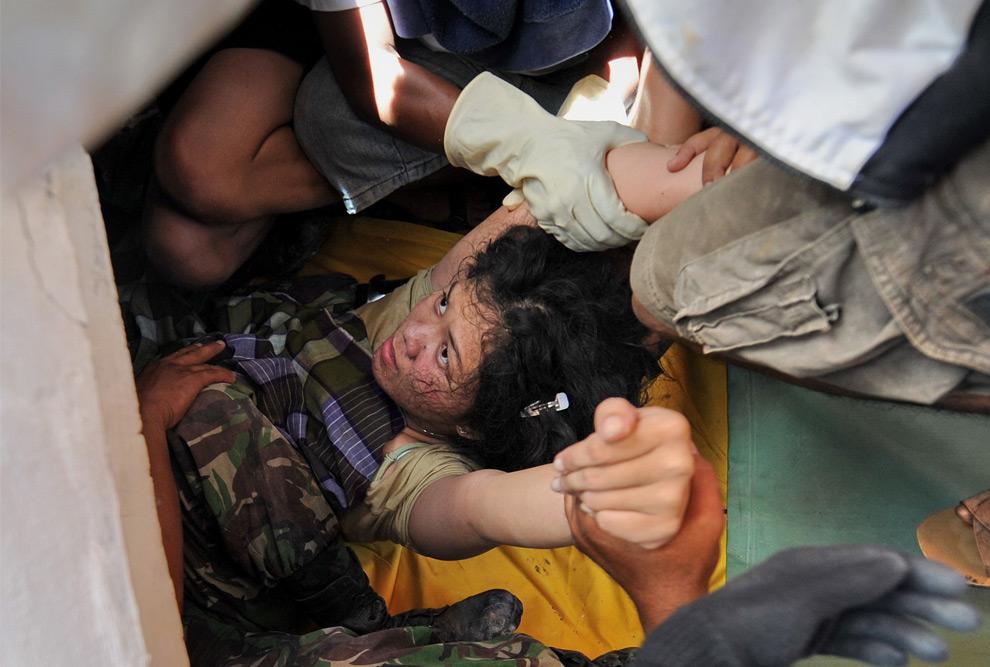 12. Индонезийскую женщину по имени Сури достают из-под обломков здания в Паданге на острове Суматра 2 октября 2009 года после того, как вечером 30 сентября 7,6-балльное землетрясение сравняло здания с землей. (ROSLAN RAHMAN/AFP/Getty Images)