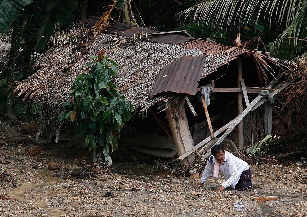 14. Мужчина пробивается через грязь перед разрушенным домом в деревне после оползня, вызванного землетрясением в Капало Кото в Париамане, провинция Западная Суматра, 5 октября 2009 года. (REUTERS/Nicky Loh)