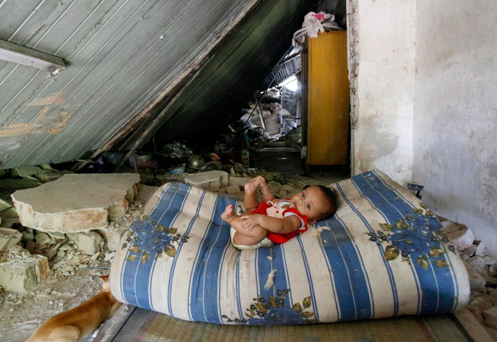 15. Ребенок на матрасе в разрушенном землетрясением доме в приморском городе Паданг в провинции Западная Суматра 4 октября 2009 года. (REUTERS/Crack Palinggi)