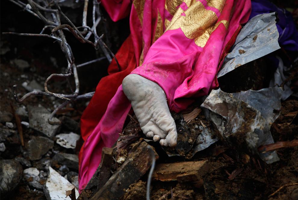 17. Нога жителя деревни, погибшего от оползня, вызванного землетрясением, видна из-под обломков в деревне Джуманак в Паданге, Индонезия, в воскресенье 4 октября 2009 года. (AP Photo/Kevin Frayer)