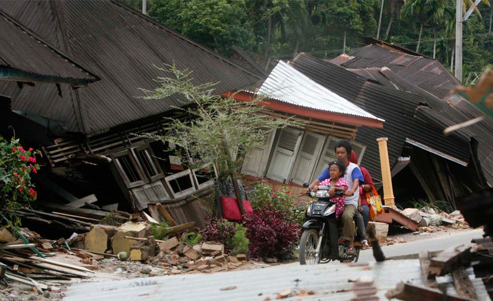 19. Семья проезжает на мотоцикле мимо разрушенных домов в деревне Патамуан в Паданге, Индонезия, 3 октября 2009 года. (REUTERS/Crack Palinggi)