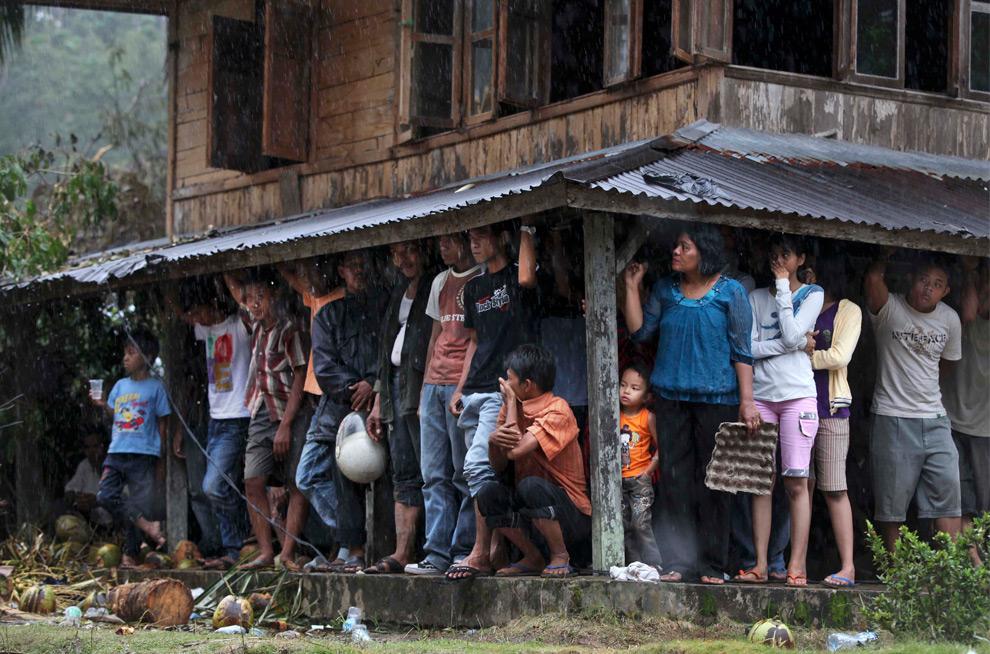 21. Жители индонезийской деревни Джуманак прячутся от дождя в районе, где вызванный землетрясением оползень уничтожил сотни домов, в воскресенье 4 октября 2009 года. (AP Photo/Kevin Frayer)