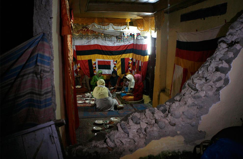 24. Гости на традиционной свадебной церемонии Рони Густиаван и Эви Сусанти сидят у разрушенной землетрясением стены 4 октября 2009 года. (REUTERS/Erik de Castro)
