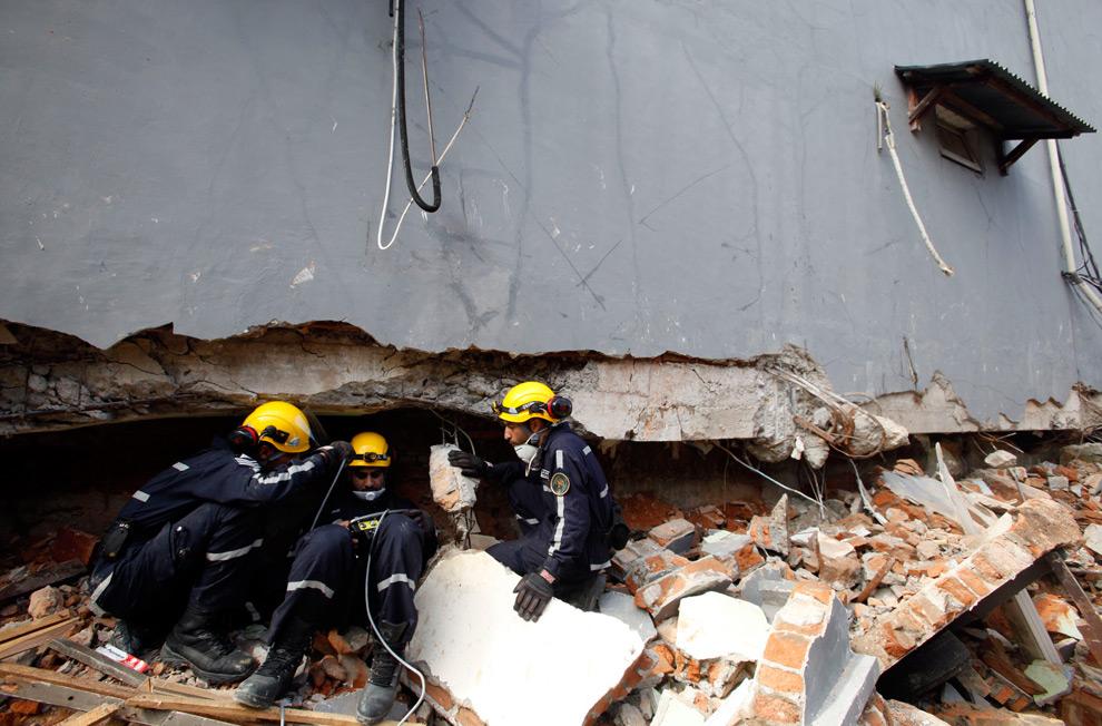 26. Спасатели из Турции с помощью специального прибора ищут под обломками здания выживших в Паданге, провинция Западная Суматра, 4 октября 2009 года. (REUTERS/Nicky Loh)