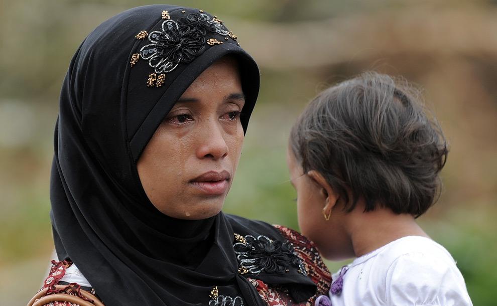 27. Индонезийская женщина оплакивает свою семью недалеко от места, где ее родные были заживо похоронены под завалами в городе Тандикет на Суматре 3 октября 2009 года. (MANAN VATSYAYANA/AFP/Getty Images)
