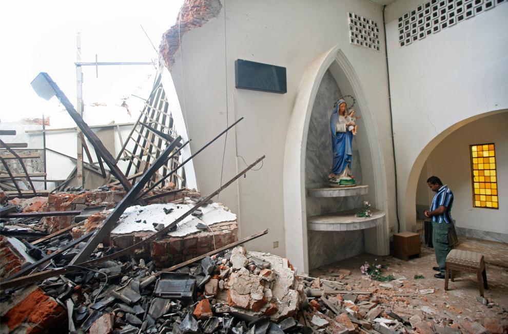 28. Мужчина молится перед статуей Девы Марии с младенцем Иисусом в католической церкви, пострадавшей в землетрясении, в воскресенье 4 октября 2009 года в Падонге, Индонезия. (AP Photo/Binsar Bakkara)