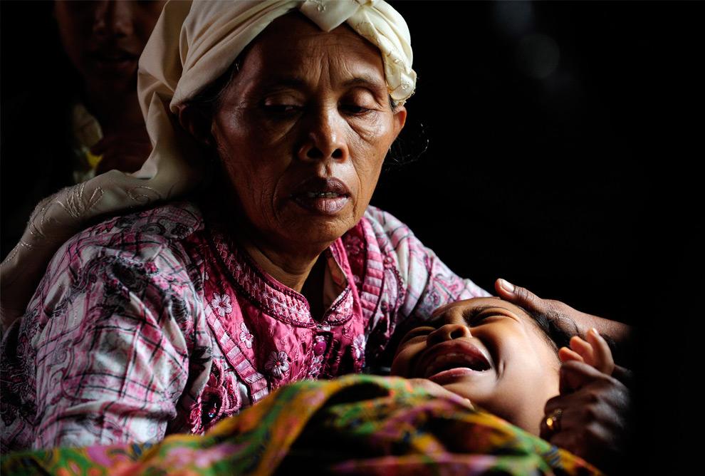 29. 9-летняя Инда, сломавшая обе ноги, кричит от боли в объятиях своей бабушки в самодельной палатке, возведенной у частично разрушенной больницы М Джамиль в Паданге, Индонезия, 3 октября 2009 года. (REUTERS/Dylan Martinez)
