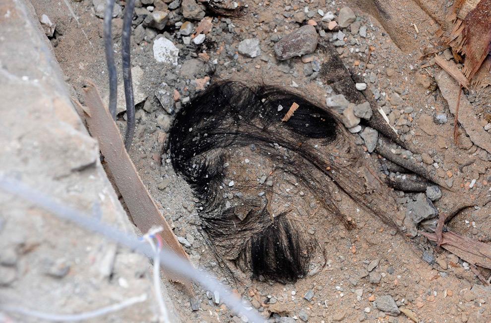 32. Только волосы погибшей видны из-под обломков разрушенного здания в центре Паданга рано утром 4 октября. (REUTERS/Dylan Martinez)