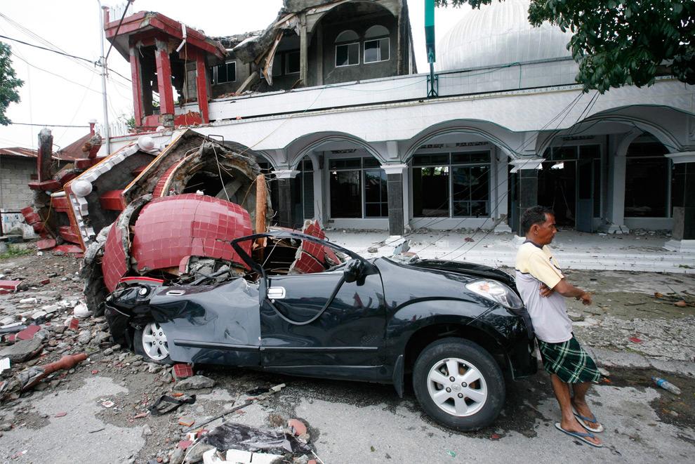 33. Мужчина опирается на автомобиль, на который упал минарет мечети после землетрясения в Паданге, Западная Суматра, Индонезия, 1 октября 2009 года. (AP Photo/Dita Alangkara)