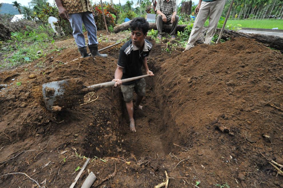 34. 26-летний Насирван копает могилу собственному отцу, погибшему в землетрясении 30 сентября в деревни Лубук Лавех в Париамане, Западная Суматра, 5 октября 2009 года. (BAY ISMOYO/AFP/Getty Images)