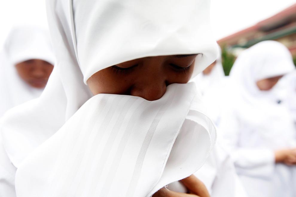40. Студентка плачет во время молитвы в школе после возобновления занятий после землетрясения в Паданге, провинция Западная Суматра, 5 октября 2009 года. (REUTERS/Dadang Tri)
