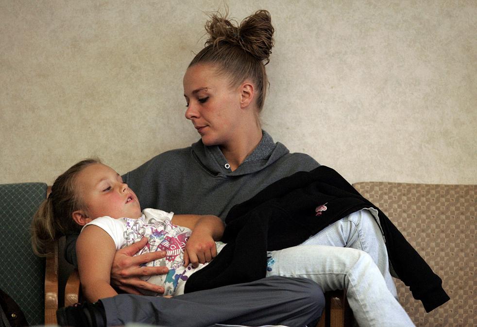 3. 23-летняя Мелисса Беннетт из Южного Бенда сидит со своей 5-летней дочерью Дестени в приемной; девочку должны проверить на симптомы свиного гриппа в семейном медицинском центре в Грейджере, штат Индиана, в среду 7 октября. Вирус H1N1 пришел в Южный Бенд примерно месяц назад. В газетах Южного Бенда сообщается, что во вторник в больницу поступила 11-летняя Мерседес Льюис с симптомами, включающими больное горло. Девочка умерла, хотя до понедельника считался совершенно здоровой. (South Bend Tribune / Jim Rider)