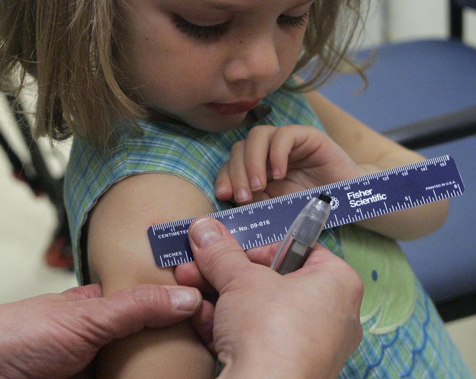 5. Трехлетняя Дреннан Барнс смотрит, как сестра измеряет след от укола после введения вакцины от свиного гриппа на ее левой руке во время клинического обследования для детей в детском центре Эмори 2 сентября в Атланте. (AP / John Amis)