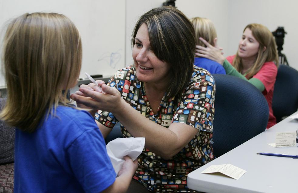 6. Медсестры Мишель Ламберт (вторая слева) из Управления здравоохранением округа Кливленд и Энжи Стродерман (справа) из Управления здравоохранением округа МакКлэйн делают детям вакцинацию против свиного гриппа с помощью носовых спреев в начальной школе в Ньюкасле, штат Оклахома, в среду 7 октября. (AP / Sue Ogrocki)