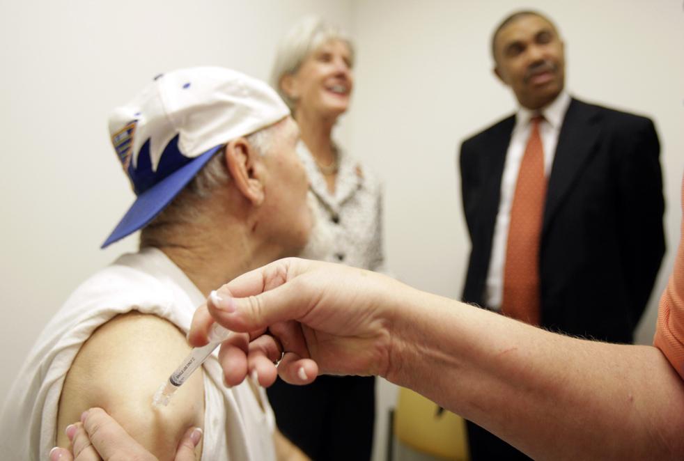 12. Майк Кастлинг (слева) участвует в программе изучения вакцины против вируса H1N1 в университетском центре Сент-Луиса; на заднем плане стоят министр здравоохранения и социального обеспечения Кейтлин Себелиус (в центре) и представитель правительства США Лэси Клэй. Во вторник 6 октября в центре проводилась программа разработки вакцины против вируса H1N1. (AP / Jeff Roberson)