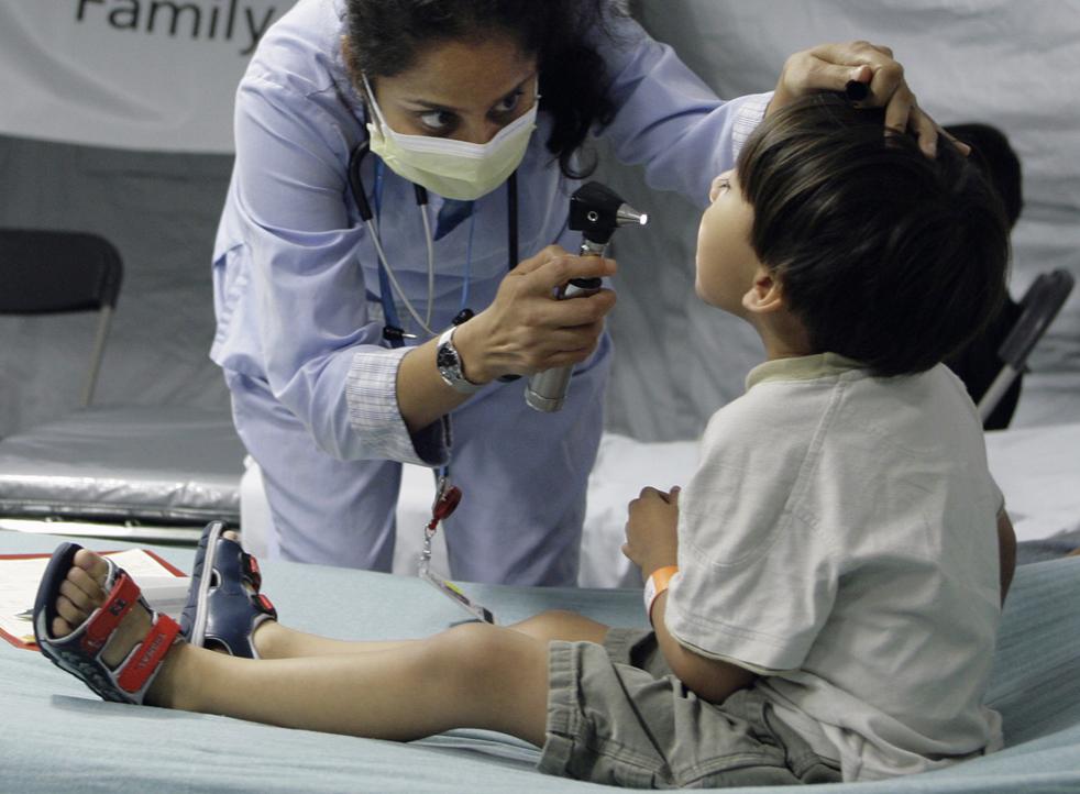 14. Доктор Торал Шах осматривает 4-летнего Сами Джиминез в клинике, где пациентов осматривают на симптомы свиного гриппа в детской больнице Делл в понедельник 28 сентября в Остине, штат Техас. (AP / Harry Cabluck)
