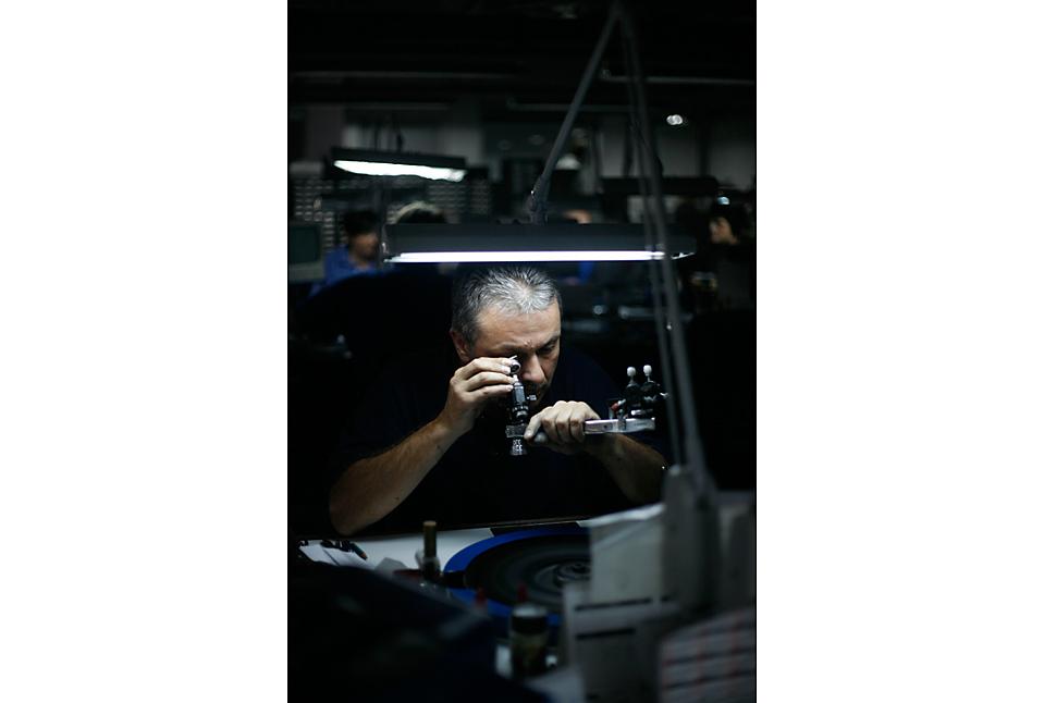 3. Рабочий за шлифовальным кругом изучает грань, которую он вырезал в бриллианте на заводе компании «Laurelton Diamonds» в Антверпене, Бельгия. (Pierre Terdjman/Gamma for The Wall Street Journal)