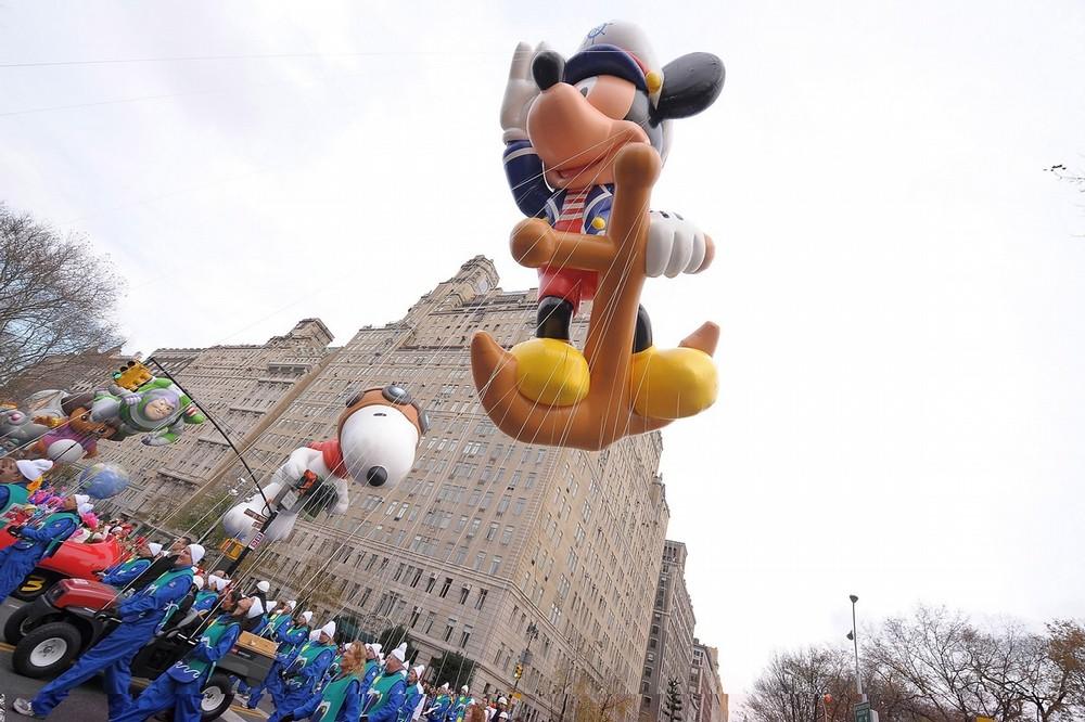 8) Надувные фигуры Снупи и Микки-Мауса Моряка пролетают над толпой на одной из улиц Манхэттена. (Michael Loccisano/Getty Images)