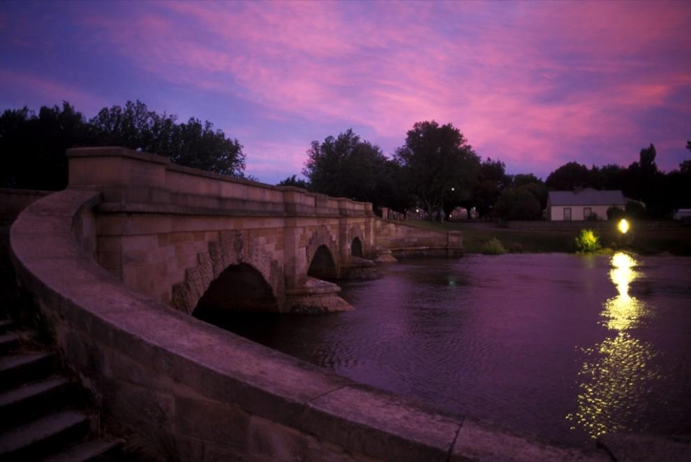 1. На этом снимке мост Росс в Тасмании окутан розовато-лиловым рассветом. Красивый пролет моста из песчаника, построенного в 1836 году, - один из самых старых в Австралии и украшен внушительной резьбой. (Sam Abell)