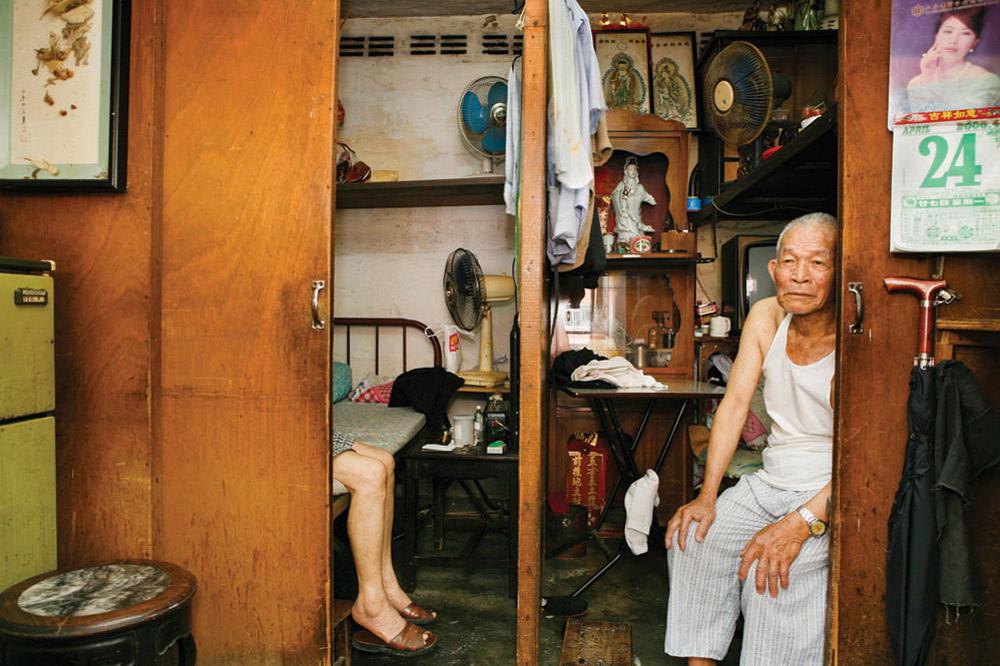 18. 94-летний Со Шеунь жил в общежитии Шек Кип Мей 25 лет. Он все жизнь проработал курьером продуктов в рестораны. Что ему нравится в этом месте больше всего? Низкая арендная плата. (Michael Wolf/ New York Times Lens)