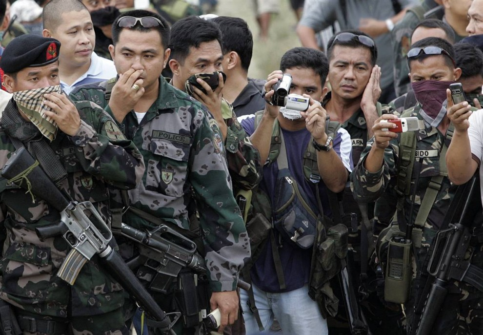 1) Полиция и военнослужащие смотрят на обнаруженные тела, которые достали из массового захоронения на склоне холма в муниципалитете Ампатуана на юге Филиппин.