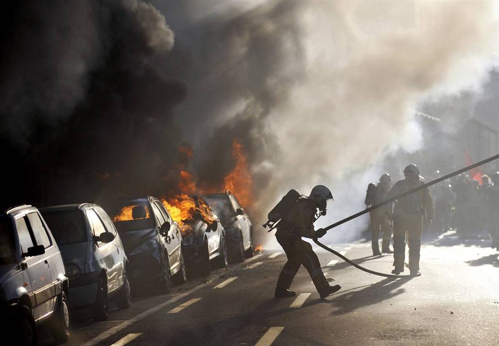 7) Пожарные бегут к горящим автомобилям после столкновений в центре Женевы, в субботу, 28 ноября. Демонстранты шли против новой всемирной встречи торговую организацию. (Fabrice Coffrini/AFP - Getty Images)