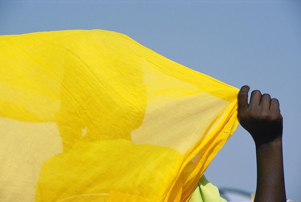 1. На этом снимке женщина в Диафарабе, Мали, держит свой ярко-желтый шарф на фоне голубого африканского неба. Ее страна представляет собой пустыню, которая когда-то была центром древних сахарских маршрутов караванов. (Michael S. Lewis)