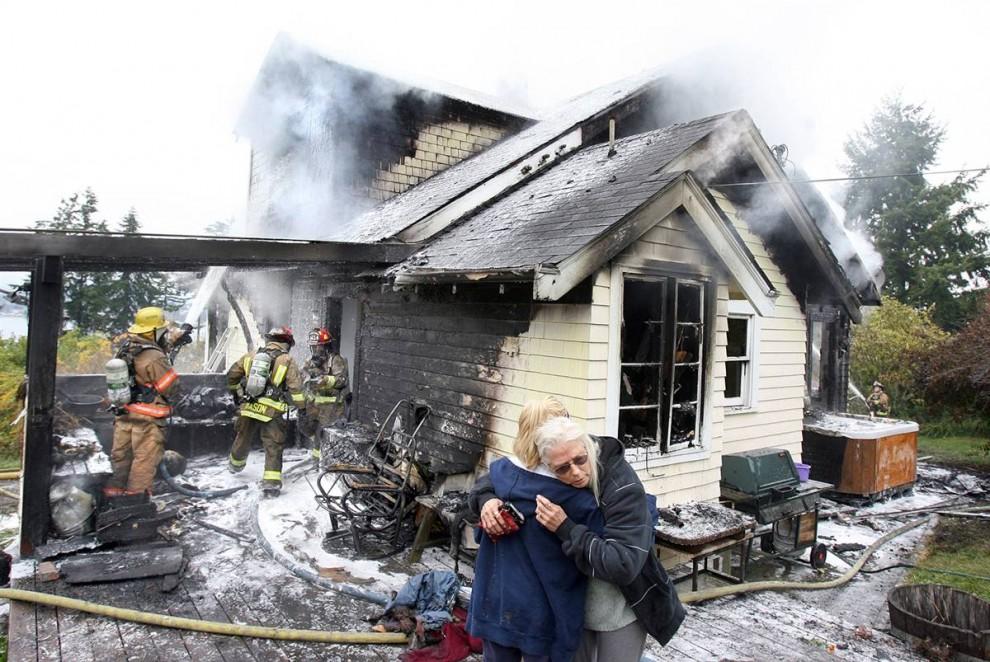 2. Родственница успокаивает Джуди Пембл (справа) у ее домика 1900-ых годов, который сгорел в Порт Орчад, штат Вашингтон, 31 октября. Дом сгорел полностью, но никто из жильцов не пострадал. (Larry Steagall / Kitsap Sun)