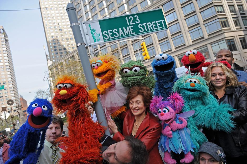 2. 9 ноября 2009: куклы Улицы Сезам и их кукловоды позируют рядом с временным знаком на West 64th Street и Бродвее в Нью-Йорке накануне 40-летия легендарного детского телешоу.