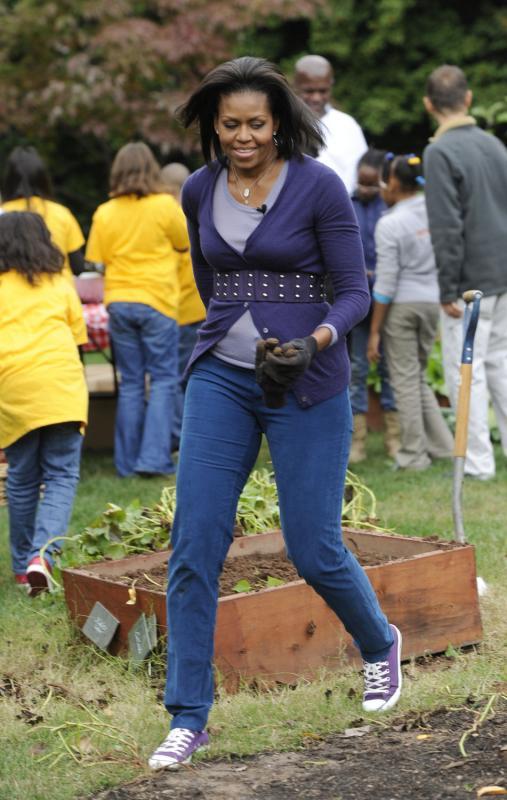 2. Первая леди Мишель Обама работает со школьниками из начальных школ Банкрофт и Кимболл во время сбора урожая в Вашингтоне 29 октября 2009 года. (UPI/Alexis C. Glenn)