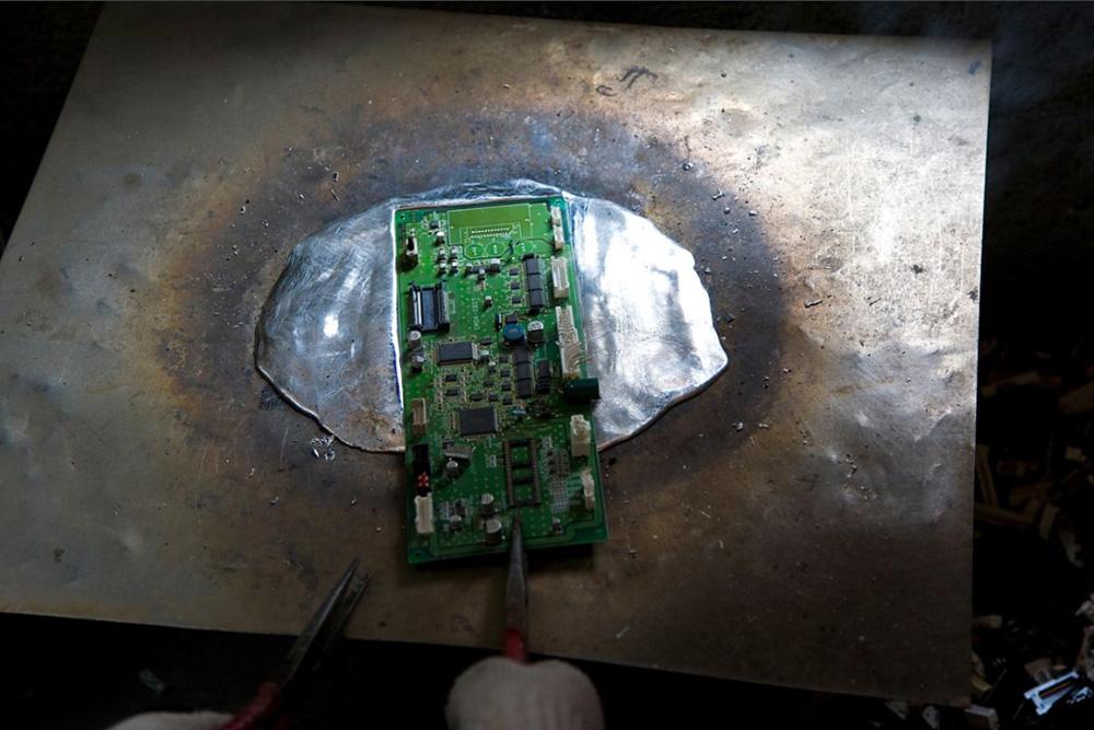 2) Компьютерную плату нагревают на стальной поверхности, чтобы вытащить из нее чипы.
