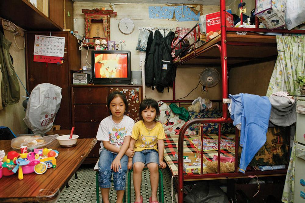 17. 9-летняя Джин Хой Йинг и 5-летняя Вонг Кван Тинг все жизнь прожили в общежитии Шеек Кип Мей. Больше всего в этом месте им нравится то, что есть где поиграть, а также приятные дружелюбные соседи. (Michael Wolf/ New York Times Lens)
