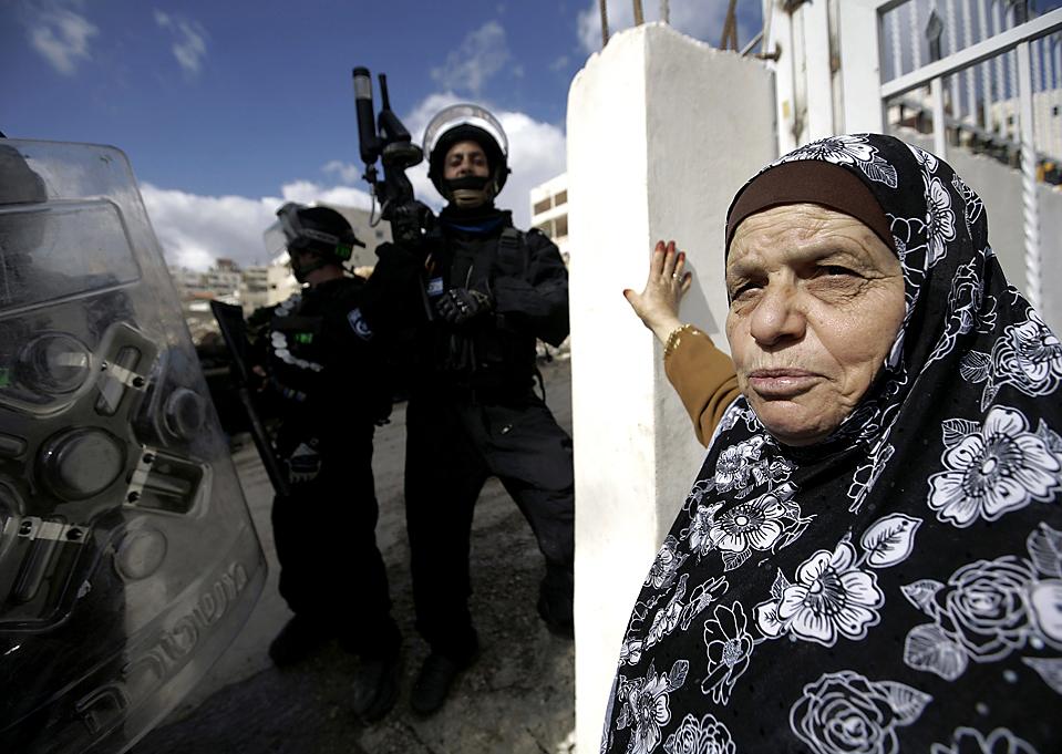 2) Старая палестинка стоит рядом с израильскими полицейскими во время сноса ее дома в районе Исавия, в Восточном Иерусалиме. (Ammar Awad/Reuters)