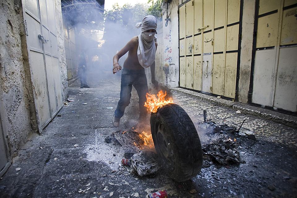 2) Палестинский подросток поджег шину во время столкновений с израильской полицией в Старом городе Иерусалима. Десятки людей были ранены в ходе столкновений между израильской полицией и палестинцами в мечети Аль-Акса, месте священном для мусульман и евреев. (Jonathan Nackstrand/AFP/Getty Images)