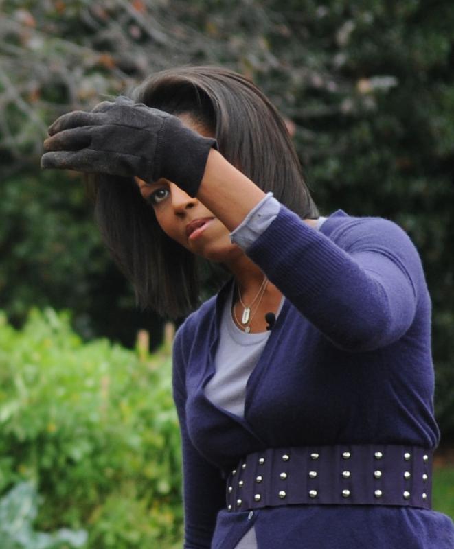 3. Первая леди Мишель Обама держит червяка во время сбора урожая  с учениками школ Банкрофт и Кимболл на огороде Белого Дома 29 октября 2009 года. (UPI/Alexis C. Glenn)