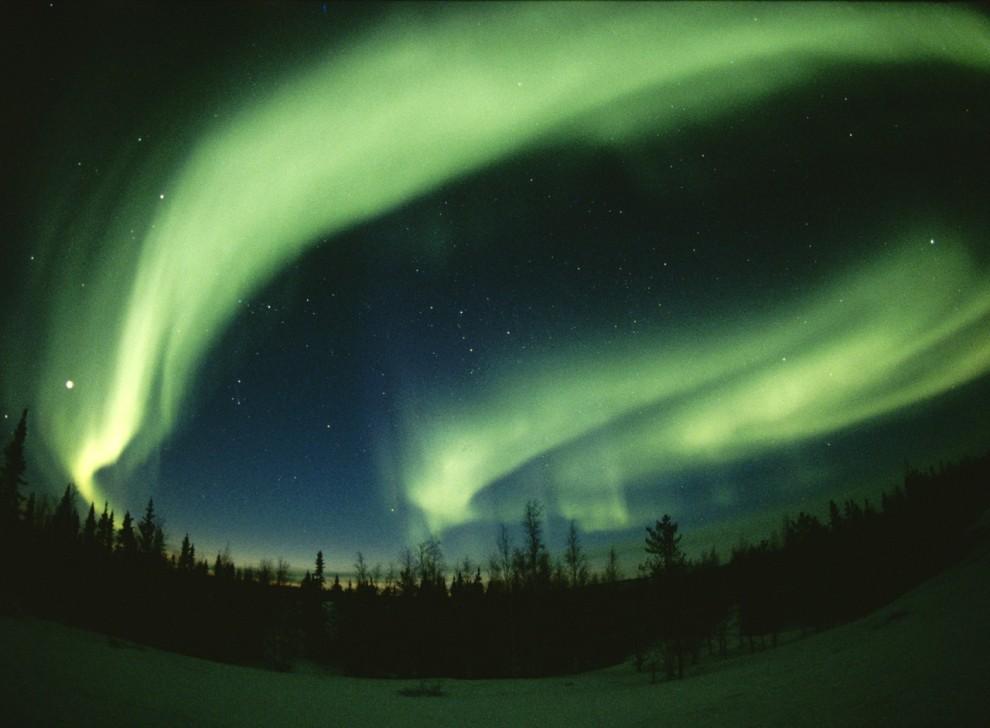 3. Северное сияние образует невероятные узоры в небе недалеко от Йеллоунайф, Канада. Этот феномен природы возникает из-за действия солнечного ветра (потоков частиц, выброшенных Солнцем) в атмосфере на полюсах Земли. (Paul Nicklen)