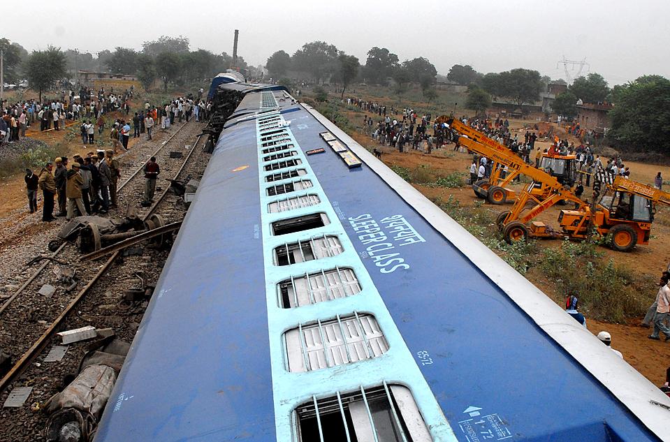 3) Спасатели и зеваки собрались на месте крушения поезда Мандор Экспресс в индийской деревне Jhar. Поезд, курсирующий между популярными туристическими направлениями Индии Джодхпур и Нью-Дели, опрокинулся на железнодорожных путях рано утром. (STR/AFP/Getty Images)
