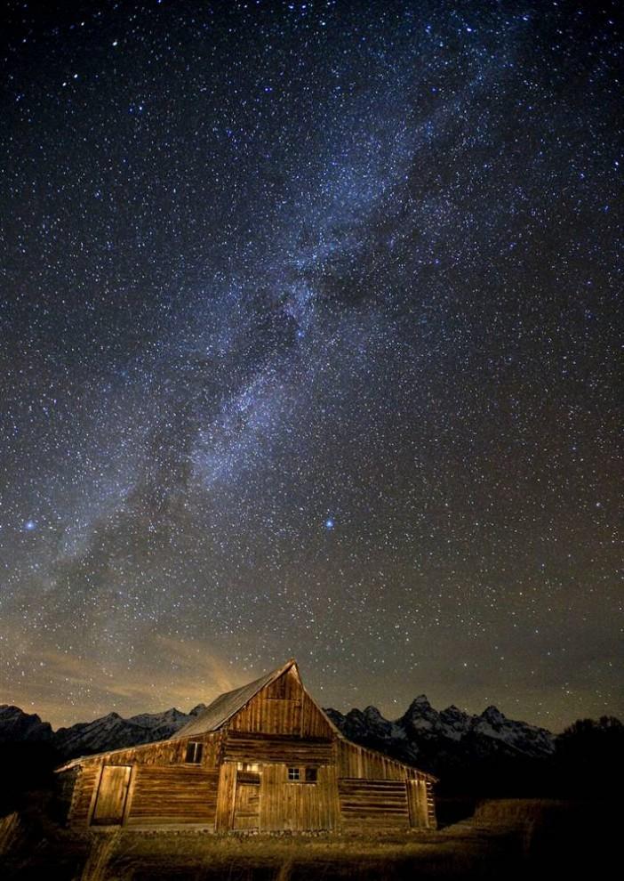 3. Млечный Путь распростерся по ночному небу над историческим поселением Мормон Роу в Национальном парке Гранд Тетон недалеко от Джексона, штат Вайоминг, 19 ноября. Свет вдали исходит от города Дриггс, штат Айдахо, на западной стороне горной цепи Тетон. (Bradly J. Boner / AP)