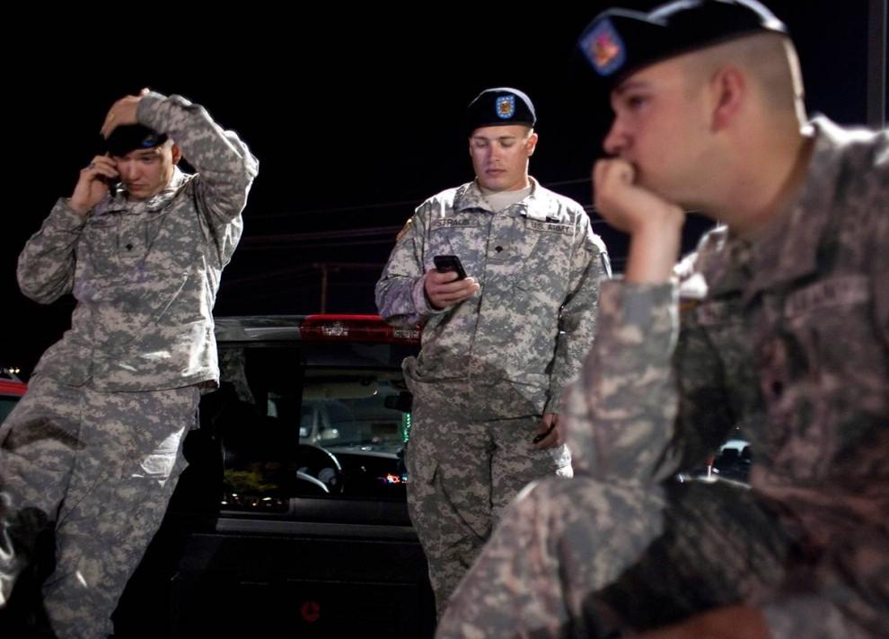 3. Военные специалисты Чад Рингс, Дэвид Штрауб и Райан Говард ждут взъезда в Форт-Худ недалеко от главного въезда на базу в четверг 5 ноября в Киллине, Техас. (Ben Sklar / Getty Images)