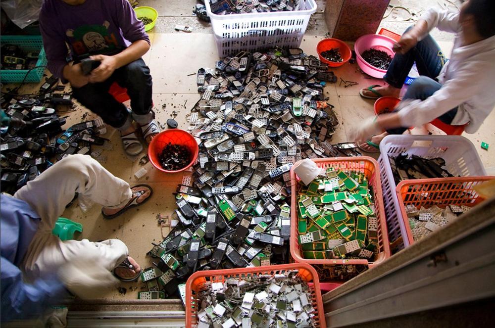 4) Рабочие ломают мобильные телефоны, разбирают их на части и сортируют.