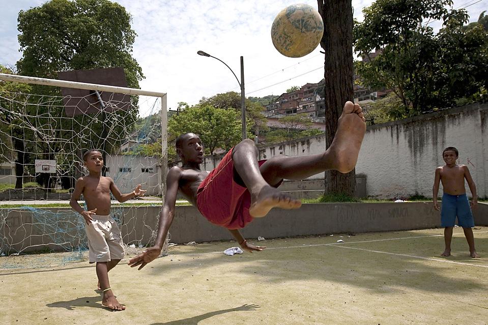 4) Уличные мальчишки играют в футбол в трущобах Morro DOS Macacos в Рио-де-Жанейро. Внимание международной общественности на прошлой неделе снова было приковано к проблеме преступности в бразильской столице, когда в кровавых перестрелках погибло более 40 человек. Это прошло всего через несколько дней после того, как Рио-де-Жанейро было избрано местом проведения Олимпийских игр 2016 года. (Felipe Dana/Associated Press)