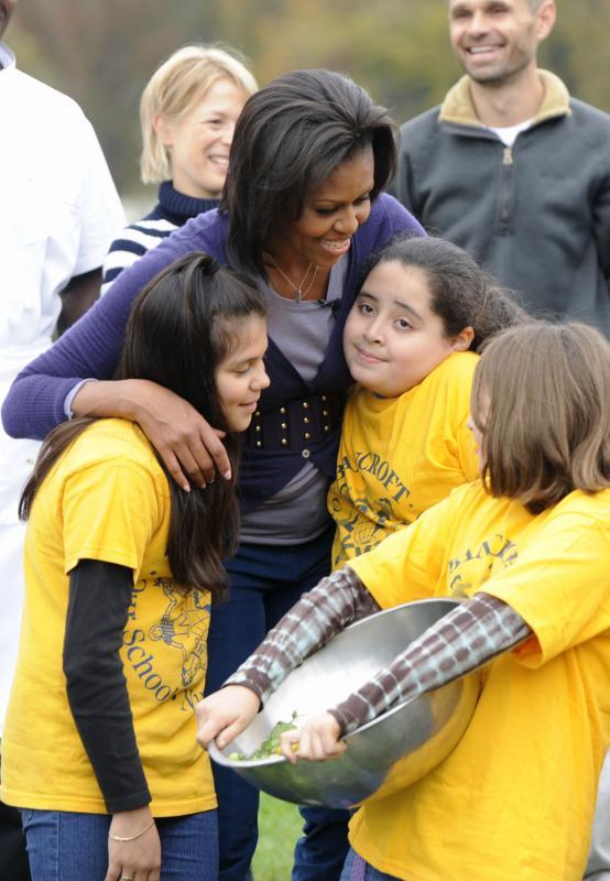5. Первая леди Мишель Обама обнимает учеников начальных школ Банкрофт и Кимболл во время совместного сбора урожая на огороде Белого Дома в Вашингтоне 29 октября 2009 года. (UPI/Alexis C. Glenn)