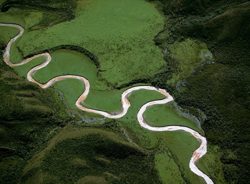 5. Вид с высоты птичьего полета на извилистую реку в горном регионе Перу Чачапойя. На зеленом фоне пейзажа можно разглядеть крошечные черные точки – это стада пасущихся животных. (Bobby Haas)