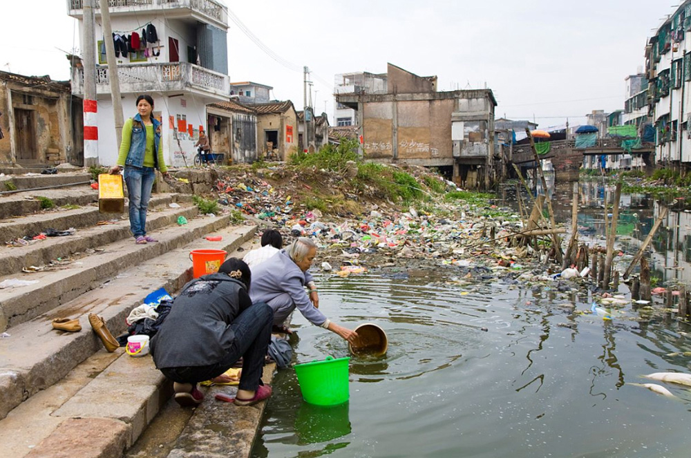 6) Жители города Гуйюй стирают одежду у берега загрязненной реки.