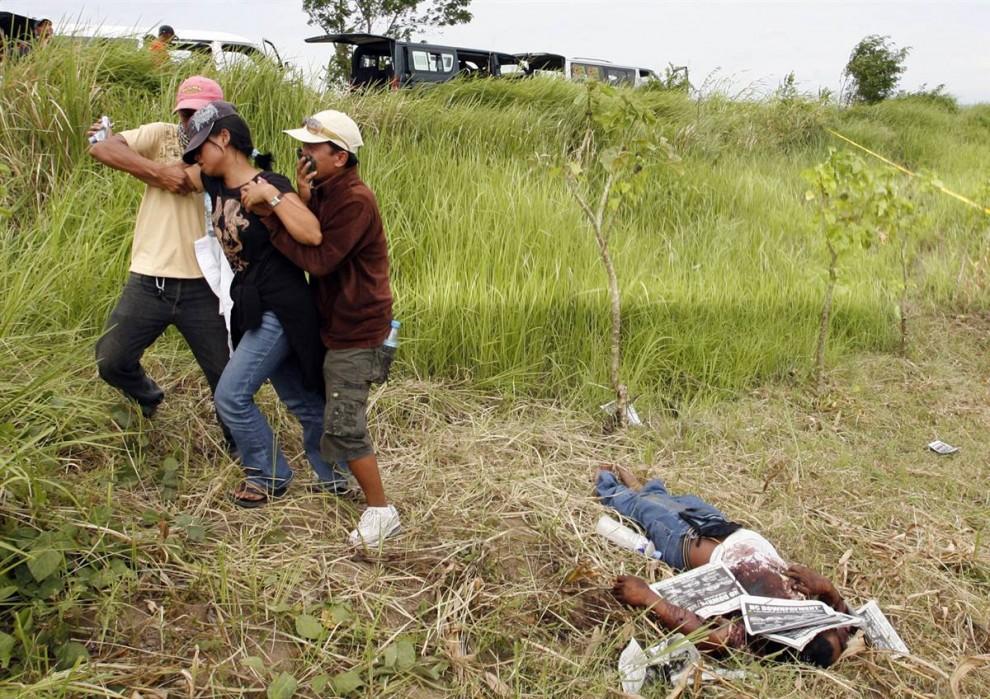 6) Женщину уводят от тела ее мужа, местного репортера, который был в числе жертв этой кровавой расправы.