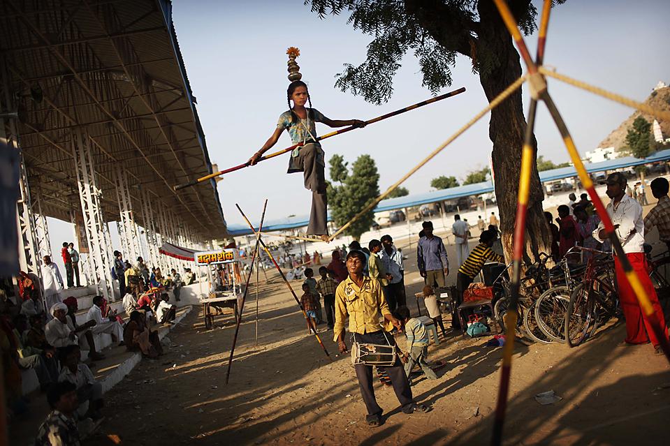 6) Девочка из уличного цирка ходит по канату во время фестиваля Пушкар Мела в индийском городе Пушкар. На фестиваль приехали тысячи торговцев скотом, которые согнали десятки тысяч верблюдов, лошадей и коров. Пушкар Мела проходит ежегодно вот уже несколько сотен лет. (Kevin Frayer/Associated Press)