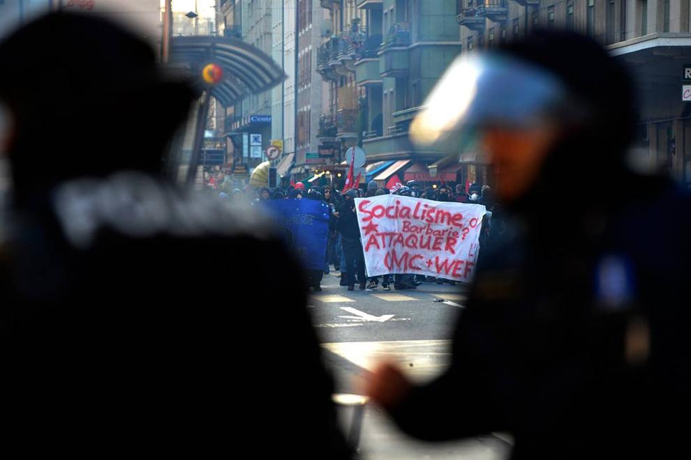 2) Полиция по охране общественного порядка противостоит демонстрантам во время марша в субботу в Женеве. (Dominic Favre/AP)