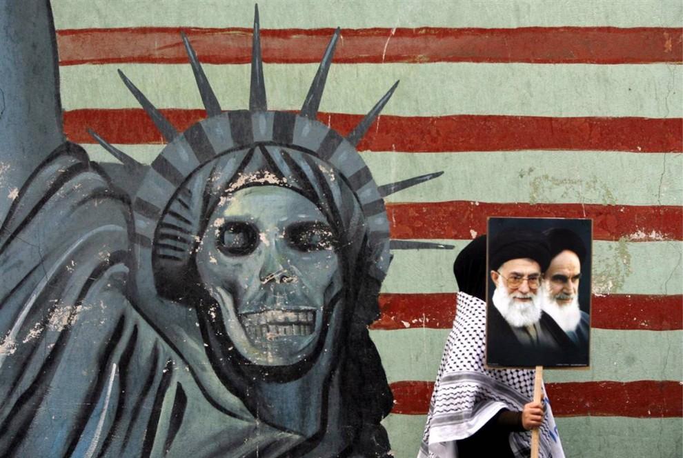 7. Иранская студентка с плакатом, изображающим иранского верховного лидера Аятоллу Али Хаменеи (слева) и покойного верховного лидера исламской революции 1979 года Аятоллу Рухолла Хоменеи проходит мимо бывшего американского посольства в Тегеране. Студентка принимала участие в демонстрации в честь 30-ой годовщины захвата посольства. (Abedin Taherkenareh / EPA)
