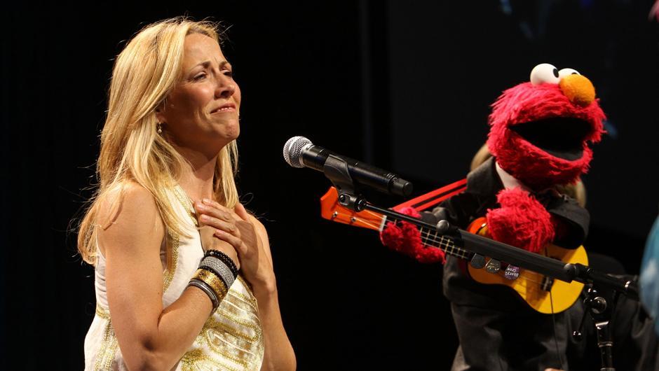 7. 27 мая 2009: певица Шерил Кроу поет с Элмо на 7-ом ежегодном гала-концерте организации «Sesame Workshop» в Нью-Йорке.