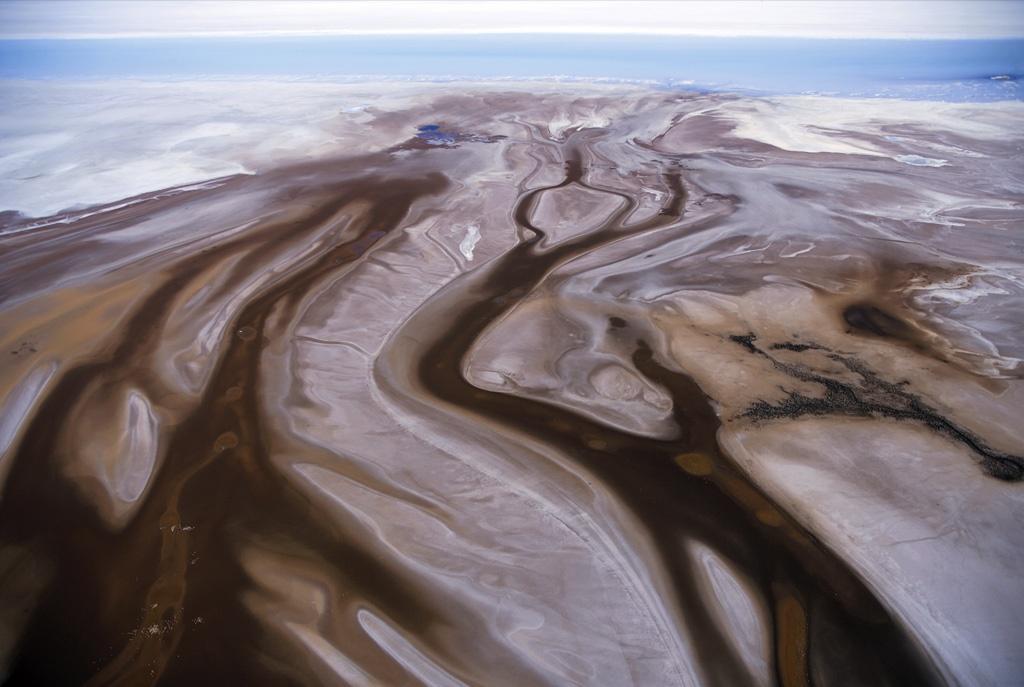 7. Простираясь к голубому соленому озеру, сухие каналы пересекают коричневые массивы Салар де Ууни – крупнейшей в мире соленой равнины. (Robert B. Haas)